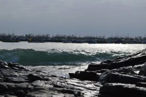 a photo of Ilo Peru water front with a close-up of a wave and boats in the background